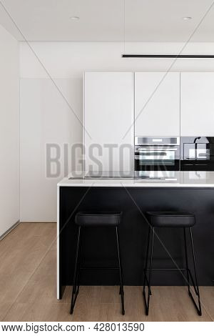 Vertical Shot Of Modern Cozy Simple Kitchen In Black And White Theme With Countertop With Glass Indu