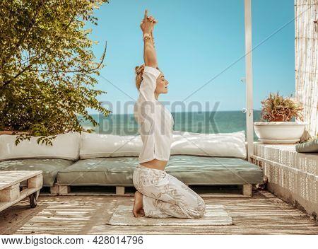 Nice Calm Female Doing Yoga Exercises on the Terrace of Beach House. Meditating on the Beach. Zen Balance. Peaceful Summer Vacation.