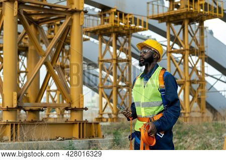 African young construction worker in equipment walking through the construction site outdoors