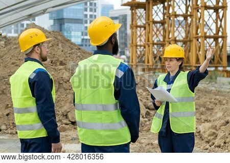 Foreman with blueprint pointing at construction and talking to workers during their work outdoors