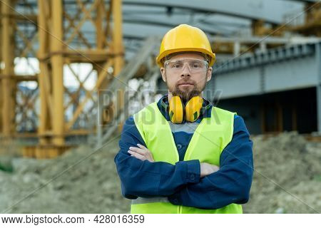 Portrait of builder in protective workwear standing with arms crossed outdoors and looking at camera
