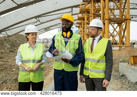 Group of engineers examining blueprint and discussing new construction project in team while walking through construction site