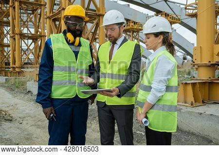 Group of construction workers in work helmets discussing project on digital tablet while standing on construction site