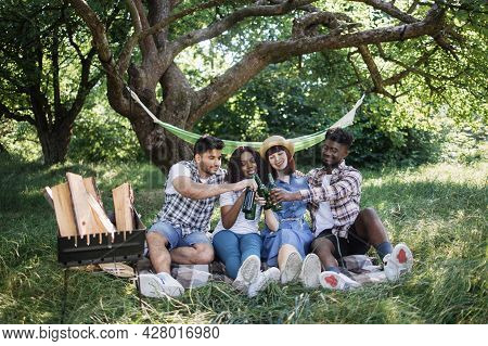 Group Of Four Multiracial Friends In Casual Clothes Sitting At Green Garden And Toasting With Bottle