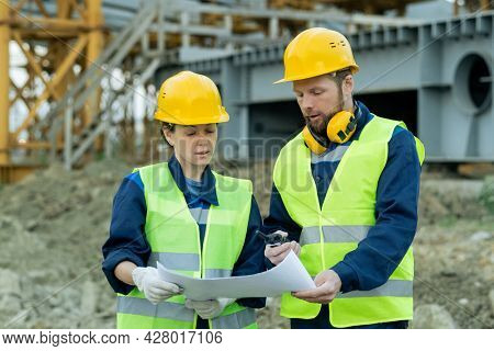 Two engineers in workwear and in work helmets examining blueprint while working in team on construction site