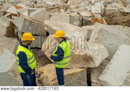 Two contemporary builders in workwear interacting between huge blocks at quarry