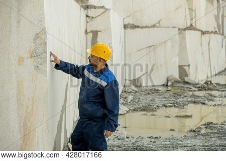 Young builder in workwear touching white block wall surrounding quarry