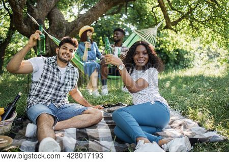 Indian Man And African Woman Relaxing On Played On Grass With Beer In Hands While Another Couple Sit
