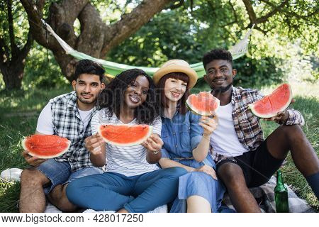 Four Cheerful Multiracial Friends Sitting At Green Garden With Slices Of Sweet Watermelon In Hands.