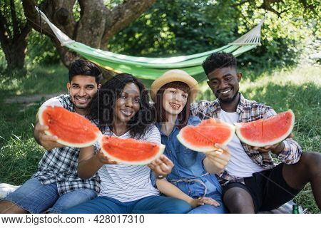 Happy Multi Ethnic Friends Enjoying Seasonal Tasty Watermelon During Picnic At Summer Garden. Four Y