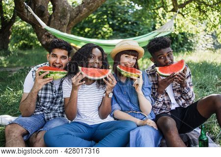 Group Of Four Multicultural People Eating Sweet Ripe Watermelon While Having Picnic At Green Garden.