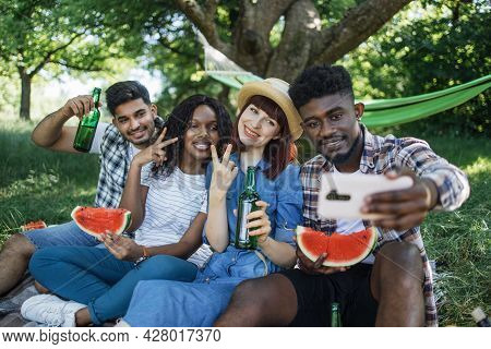Cheerful Group Of Four Diverse Friends Sitting At Green Garden With Watermelon And Beer In Hands And