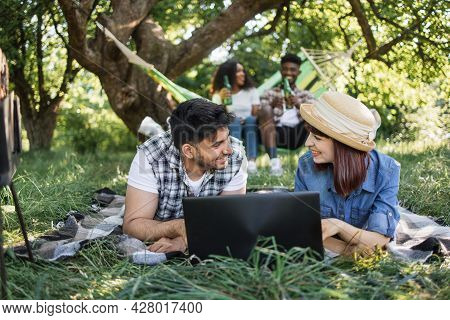 Young Indian Guy And Caucasian Woman Lying On Soft Plaid At Garden And Using Wireless Laptop. Africa
