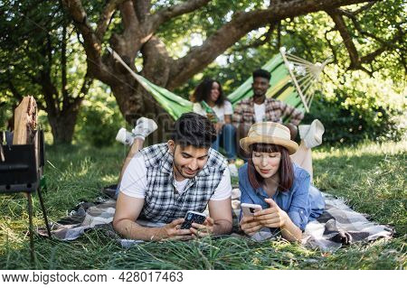 Indian Man And Caucasian Woman Resting On Soft Blanket Outdoors With Modern Smartphones In Hands. Af