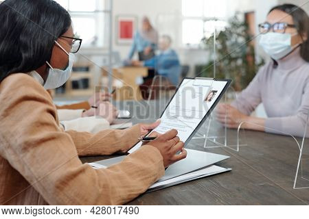 African businesswoman looking through resume of young Asian female applicant