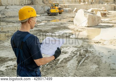 Young male builder in workwear holding sketch while standing at quarry land