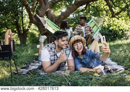 Joyful Indian Guy And Caucasian Woman Using Cell Phone For Taking Selfie. African American Couple Re