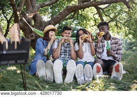 Group Of Four Multiracial Friends In Summer Clothes Sitting At Green Park And Eating Handmade Burger
