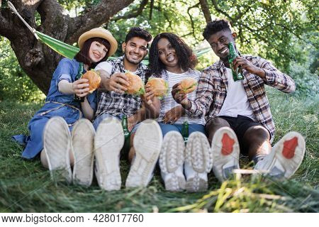 Group Of Four Multi Ethnic People Sitting On Grass With Handmade Tasty Burgers In Hands. Happy Young
