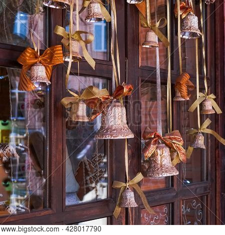 Hanging Christmas Vintage Bells On Blurred Background Of Old Wooden Window . Festive Christmas Retro