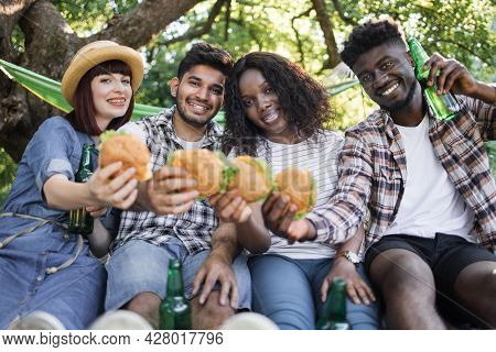 Group Of Four International Friends Enjoying Summer Picnic With Tasty Burgers And Cold Beer. Concept