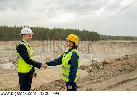 Two colleagues in hardhats and workwear shaking hands against quarry