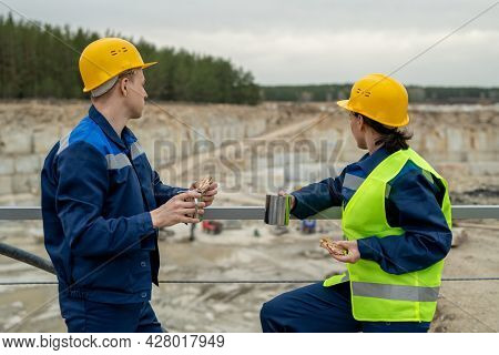 Male a nd female colleagues in workwear having rest and lunch in front of quarry
