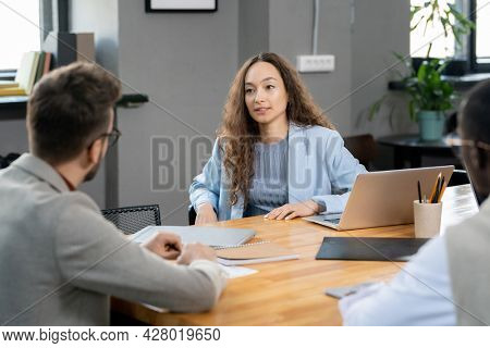 Young businesswoman looking at one of male colleagues during conversation at working meeting