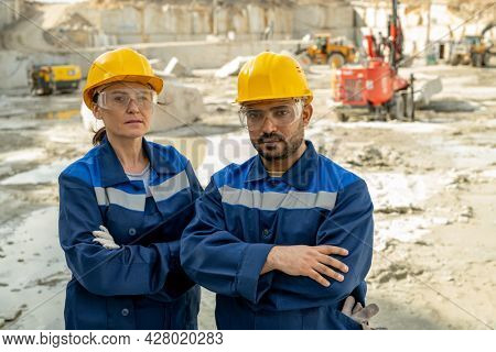 Two mature professional builders in workwear crossing arms by chest