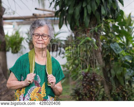 Portrait Of An Elderly Woman Exercises While Standing In A Garden. Beautiful Senior Woman Short With