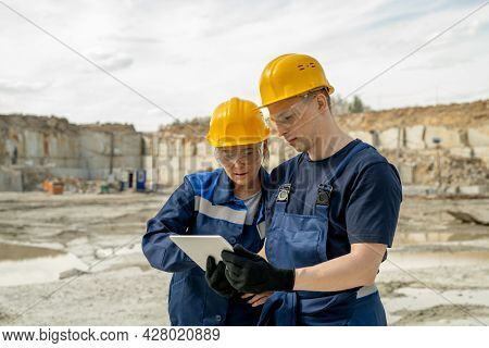 Two colleagues in workwear discussing sketch of new construction at building area