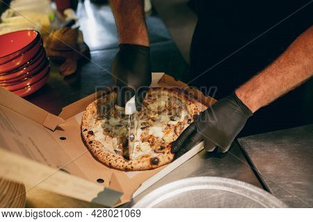 Close-up. Chef Cutting Delicious Hot Tasty Pizza Into Pieces In A Cardboard Box. Looks Tasty, Aromat