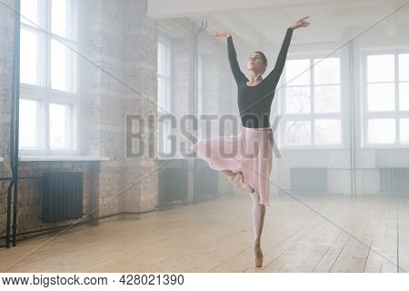Young beautiful woman ballet dancer dressed in professional outfit pointe shoes and white tutu dancing in studio