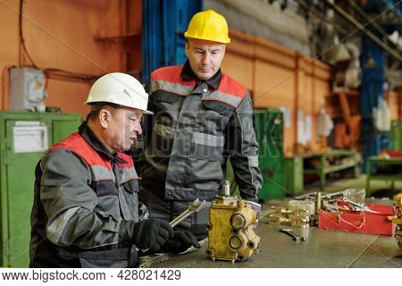 Mature engineer in workwear working with metal equipment in the machinery factory