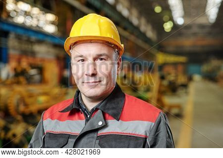 Portrait of mature manual worker in helmet and workwear looking at camera while using tablet pc in the factory