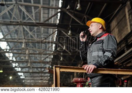 Foreman in workwear speaking in the radio set and controlling the work in the factory