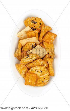 Senbei, Japanese Rice Crackers, In A White Oval Bowl. Also Sembei, Crispy, Bite-sized, Savory Snacks