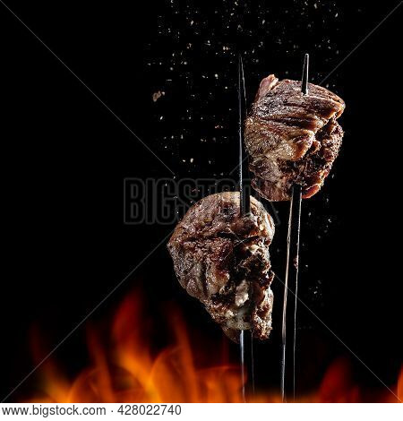Fork With Pieces Of Delicious Barbecued Meat On Black Background. Delicious Pork Pieces On Rotating