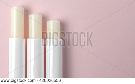 Top View Of Three Lip Balm Tubes On Pink Background.