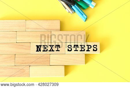 Wooden Blocks Stacked Next To Pens And Pencils On A Yellow Background. Next Steps Text On A Wooden B