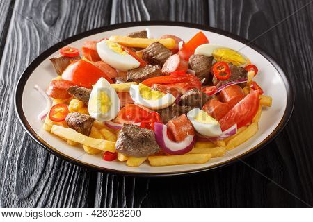 Traditional Bolivian Cuisine Spicy Multicomponent Pique Macho Close-up In A Plate On A Black Wooden