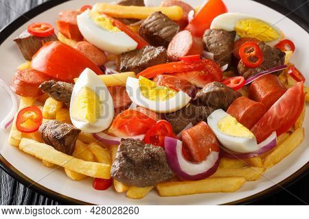 Bolivian Pique A Lo Macho Is A Dish Prepared With Cooked Meat And Sausage Served Over Fries And Garn
