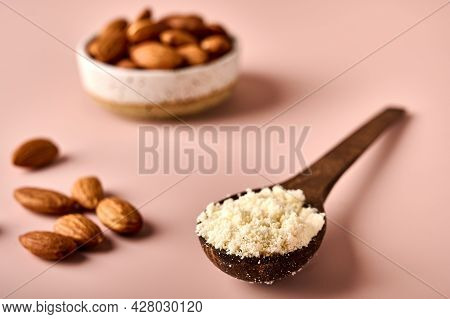 Almond Flour In Wooden Brown Spoon And Nut Kernels On Pink Powder Background. Macro. Selective Focus