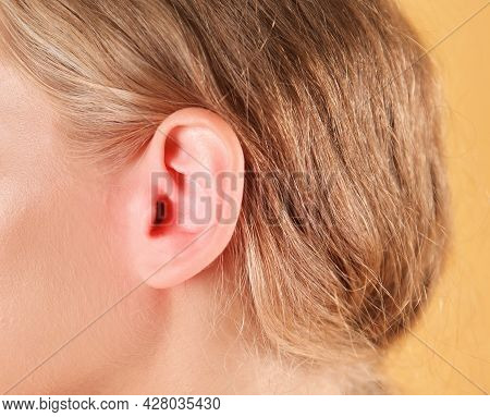 Woman Suffering From Earache On Color Background, Closeup