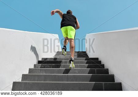 Stairs exercise fitess man running fast up the staircase for hiit cardio workout run at outdoor gym. Sport active athlete lifestyle training legs muscles.