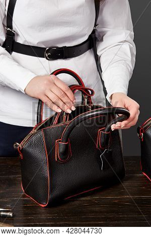 Female Master Checking Completeness Of Black Leather Bag