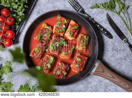 Flat Lay With Stuffed Cabbage Rolls, Tomato Sauce And Chopped Parsley On Frying Pan. Tomatoes, Parsl