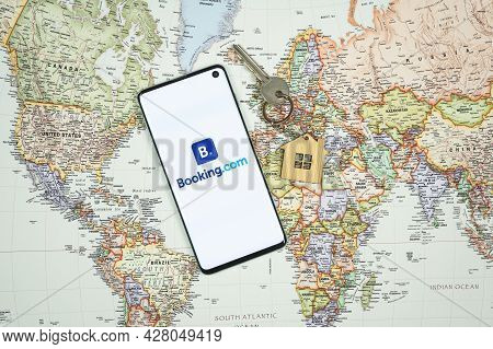 Swansea, Uk - July 4, 2021: Smartphone With Booking.com App Logo With House Keyring And Key On World