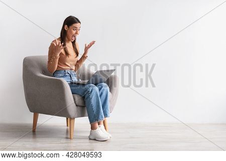 Emotional Young Woman Sitting In Armchair With Laptop, Shouting In Excitement, Winning Casino Bet, C