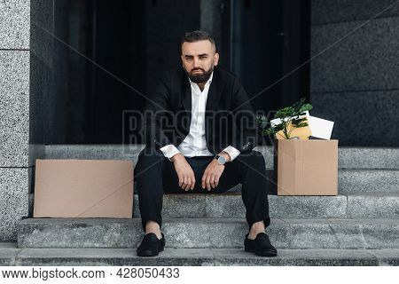 Depressed Jobless Male Office Worker With Empty Cardboard Poster And Box Of Personal Things, Sitting